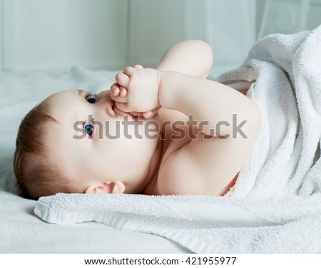 six months old baby with a towel in bed at home - stock photo