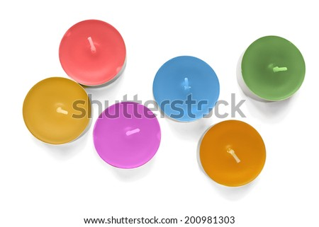 Six multicolor tea lights on white background - stock photo