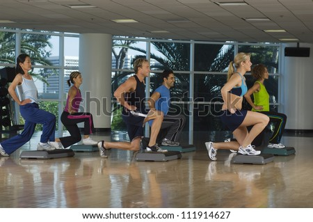 Six people exercising on step in aerobics class - stock photo