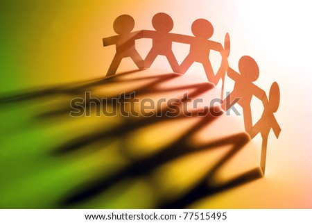 Six people holding hands, casting shadows - stock photo