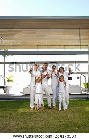 Six person family portrait in the backyard of a luxury house, gesturing thumbs up. - stock photo