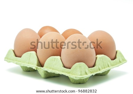 Six raw eggs in an egg cup on white background - stock photo