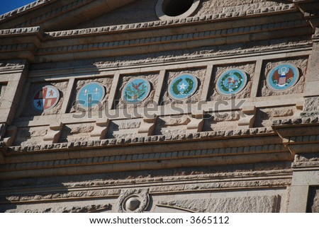six ruling nation's emblems in front of the Texas state capitol building - stock photo