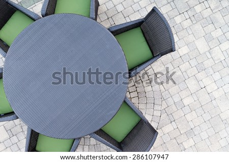 Six seater outdoor patio set with comfortable green cushions and a round dining table on a brick paved open-air patio with copy space, overhead view - stock photo