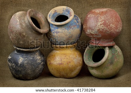 six small plant clay pots (mass produced planters) with rough color finish on dark burlap texture background, still life - stock photo