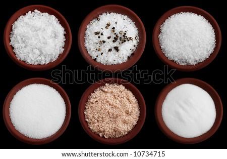 six terracotta plates with different salt - flakes sea salt, coarse sea salt with crashed black pepper, coarse sea salt, fine sea salt, smoked flaky sea salt, table salt, Isolated on black - stock photo