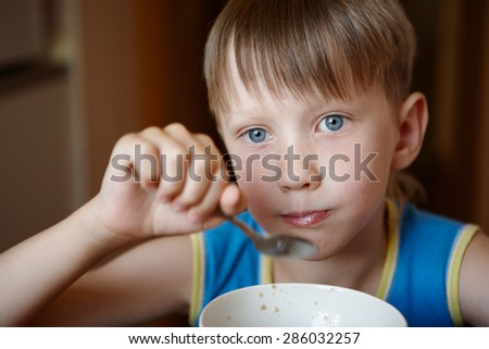 six-year boy in blue shirt eats with a spoon from a white plate - stock photo