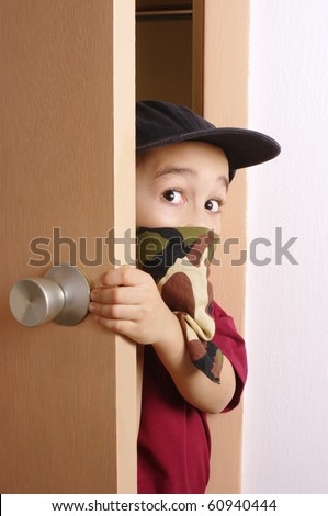 Six-year-old boy wearing a camouflage-colored bandanna mask, sneaking in through a door - stock photo