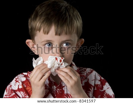 Six year old boy with a bloody nose. Horizontal framing on a black background. - stock photo