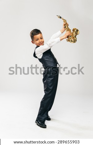 six years old boy brings saxophone over his head and laughing , side view,  - stock photo