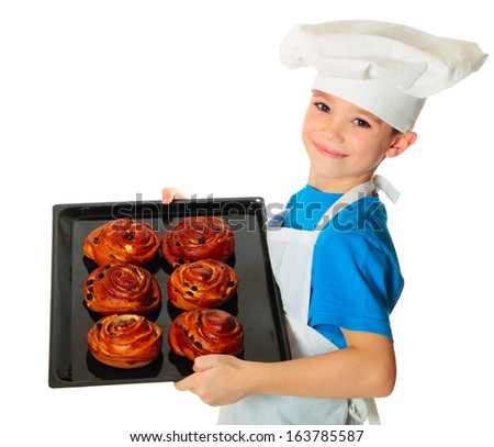 Six years old cook boy holding baking tray with fresh buns in the hand isolated on white - stock photo