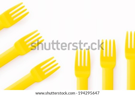 Six yellow plastic forks against a white background. - stock photo