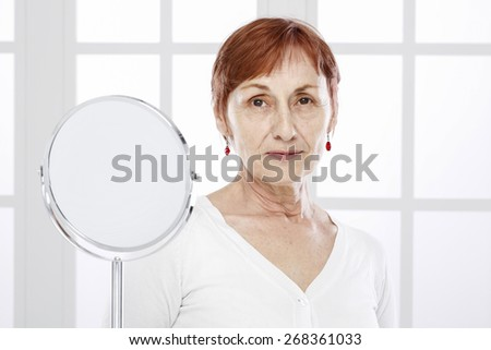 Sixty years woman and mirror - stock photo