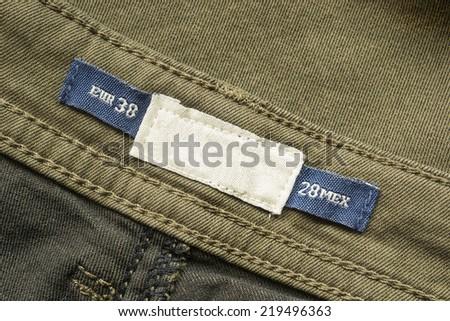 Size label on cotton khaki cloth as a background - stock photo