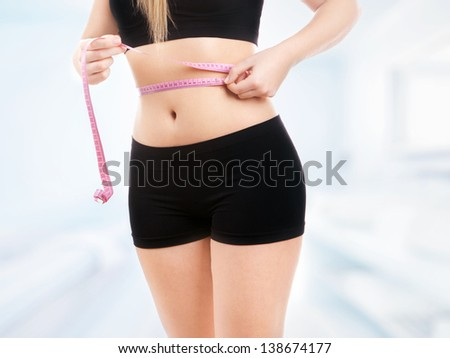 Size 36/38 woman is measuring waist - stock photo