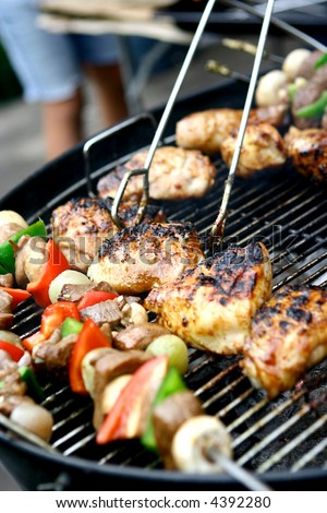 Sizzling chicken and sausages with lamb kebabs and vegetables on hot barbecue grill - stock photo