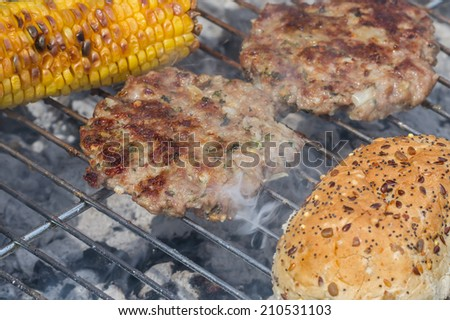 Sizzling Minted Lamb Burgers on Grill with Corn Cobs and a Seeded Bun - stock photo
