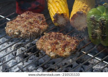 Sizzling Minted Lamb Burgers on Grill with Corn Cobs and Bell Peppers - stock photo