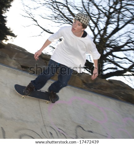 Skate boarder riding along edge of bowl - stock photo