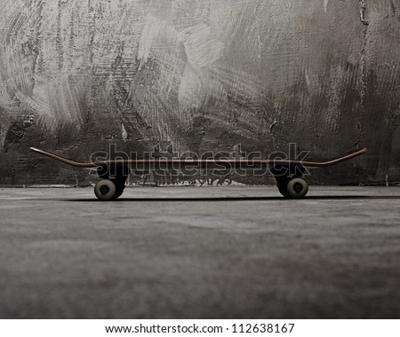 Skateboard against grunge wall - stock photo