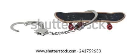 Skateboard used as simple transportation for young adults with a pair of handcuffs - path included - stock photo