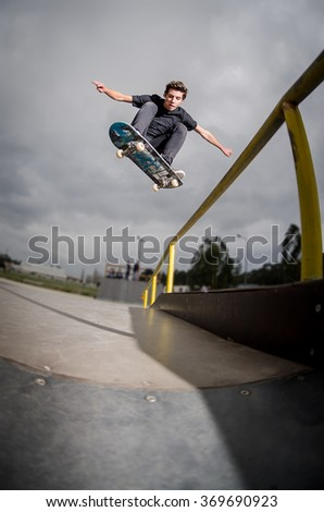 Skateboarder doing a ollie over the rail at the skate park. - stock photo
