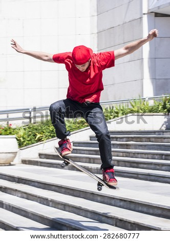 Skateboarder doing a skateboard jumping trick from  stairs - stock photo