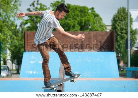 Skateboarder doing a skateboard trick at skate park. - stock photo