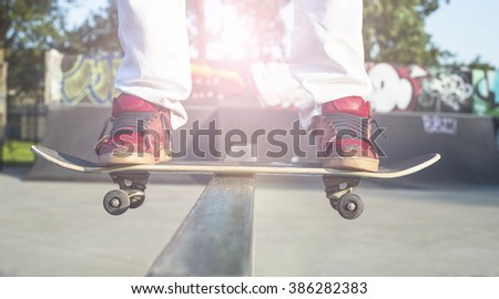 Skateboarder doing a skateboard trick at skate park. Lens flare effect - stock photo