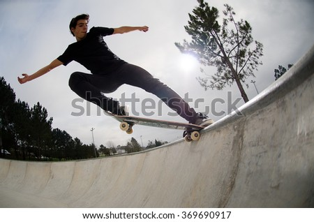 Skateboarder doing a tail slide on a croncrete pool at the skate park. - stock photo