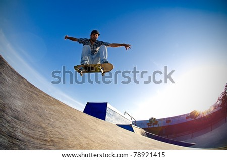 Skateboarder flying over a ramp on sunset at the local skate park. - stock photo