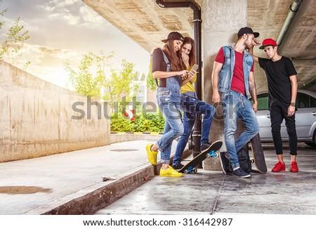 Skateboarder friends in the parking garage - stock photo