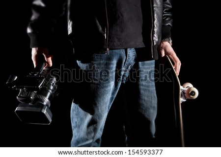 Skateboarder Holding a video camera and a skateboard isolated on black background - stock photo