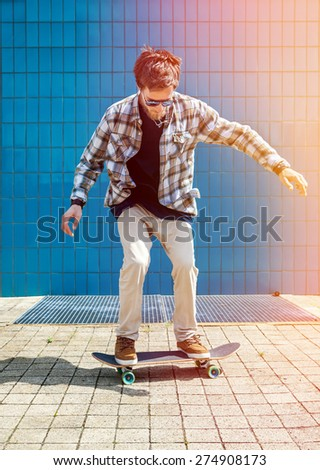 Skateboarder jumping in city on skateboard at the background wall tiles - stock photo