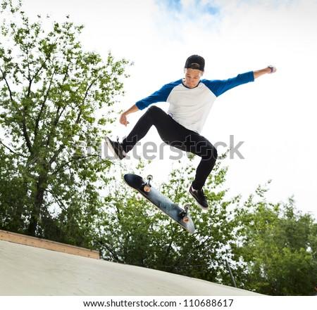 Skateboarder jumping in halfpipe at skatepark - stock photo