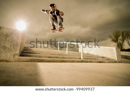 Skateboarder jumping over the stairs on a big ollie. - stock photo