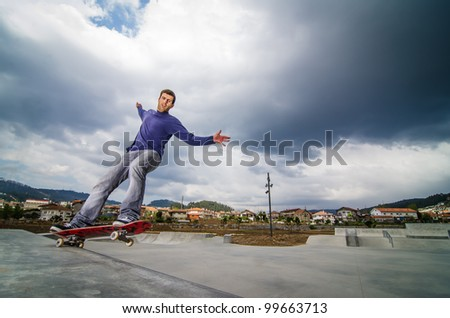 Skateboarder on a grind with dark clouds background at the local skate park. - stock photo