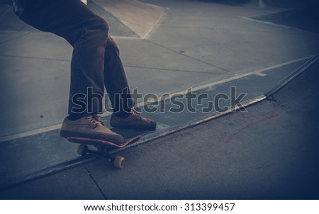 skateboarder performing a rail slide in a skate park with a shallow depth of field with a toned instagram filter with an added vignette with copy space - stock photo