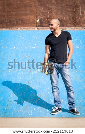 Skateboarder portrait standing on halfpipe at skate park. - stock photo