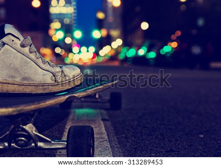 skateboarder preparing to ride down the middle of a dark city street in the late evening with a retro instagram filter with a shallow depth of field - stock photo