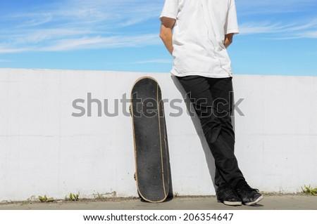 Skateboarder relax standing near the skateboard - stock photo