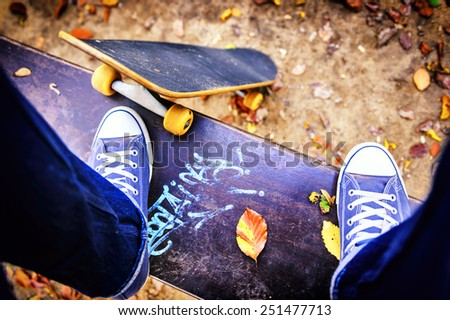 Skateboarder standing on a bench in city park  - stock photo