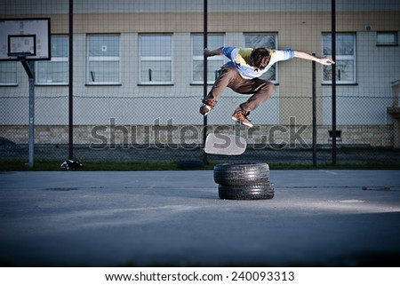 Skater doing the back side flip trick over the tyres. - stock photo
