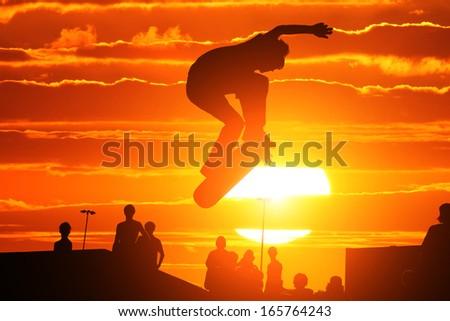 Skater on skateboard jumping over sunset sky - stock photo