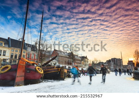 Skating in winter on a canal in a city - stock photo
