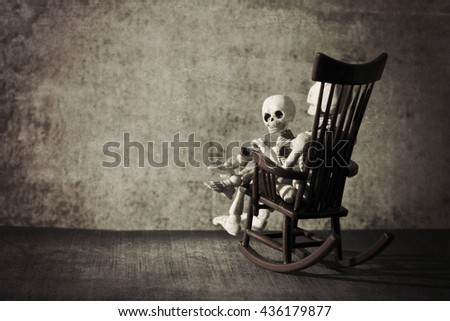 Skeleton and a little skeleton sitting in the rocking chair grungy textured - stock photo