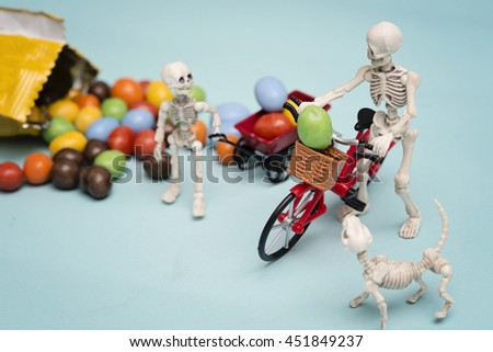 Skeleton and his skeleton kid getting chocolate candy with toy wagon and bicycle - stock photo