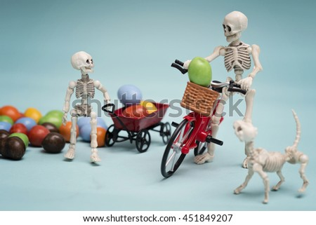 Skeleton and his skeleton kid getting chocolate candy with wagon and bicycle - stock photo