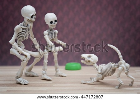Skeleton and little skeleton with bone in his hand - stock photo