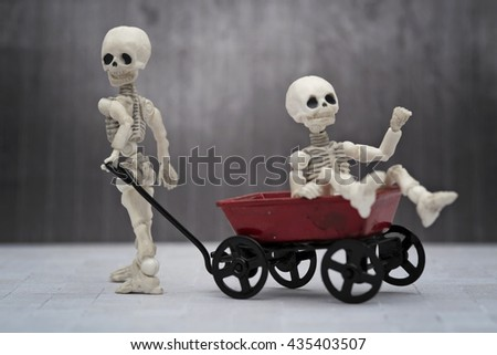 Skeleton kids playing toy wagon with black background - stock photo